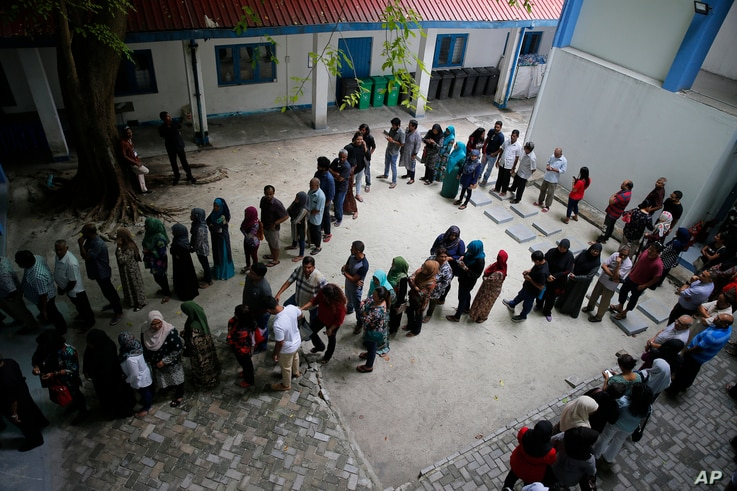 Maldivians queue at a polling station during presidential election day in Male, Sept. 23, 2018.