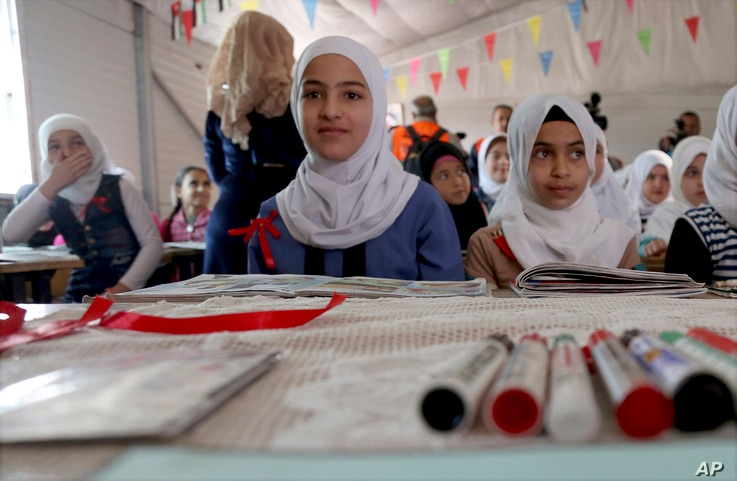 FILE - Syrian refugees pose for a photo during a visit by U.N. Secretary General Antonio Guterres to a fourth-grade classroom at the U.N.-run Zaatari camp for Syrian refugees, in northern Jordan, March 28, 2017.