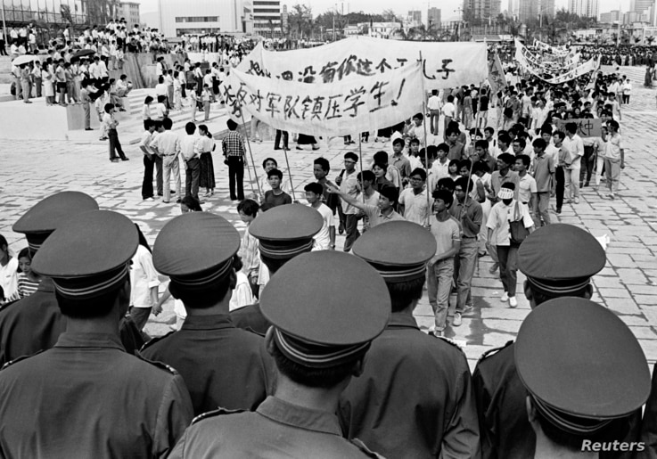 FILE - Chinese police monitor a march by tens of thousands of pro-democracy protesters in the special economic zone of Shenzhen in southern China on May 22, 1989.