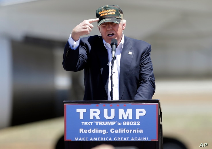 "Republican presidential candidate Donald Trump gestures to a his camouflaged ""Make America Great"" hat as he discuses his support by the National Rifle Association at a campaign rally at the Redding Municipal Airport, June 3, 2016, in Redding, Califor"