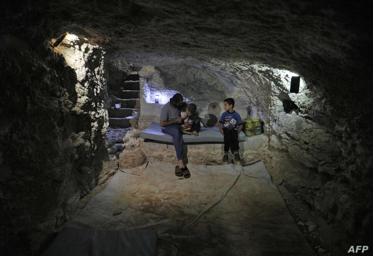Syrian Hadheefa al-Shahadh, 27, sits with his children in a cave that he dug inside his house to shelter him and his family as part of preparations for any upcoming raids in the rebel-held Idlib province's village of Maar Shurin, Sept. 11, 2018.