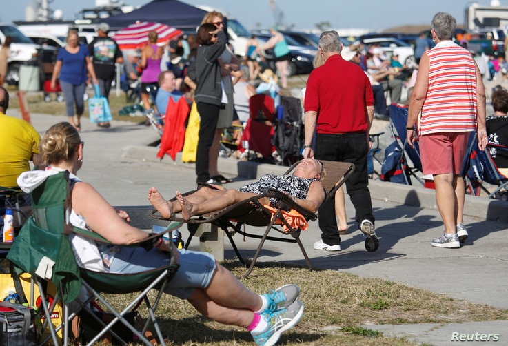 Visitors stake out spots near the fishing pier at Jetty Park to watch SpaceX's first Falcon Heavy rocket launch from the Kennedy Space Center, Florida, Feb. 6, 2018.