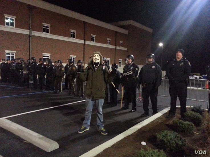 Protester in Anonymous mask posing in front of Ferguson police. He was later arrested, Nov. 19, 2014. (Ayesha Tanzeem/VOA)