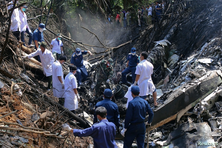Rescue workers search an air force plane crash site near Nadee village, in Xiang Khouang province, Laos, May 17, 2014.