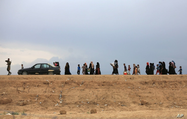 People flee their homes during fighting between Iraqi security forces and the Islamic State group during a military operation to regain control of Hit, 85 miles (140 kilometers) west of Baghdad, Iraq, Wednesday, April 13, 2016.