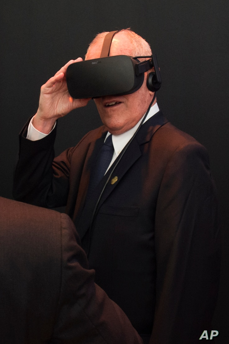 Peru's President Pedro Pablo Kuczynski tries a virtual reality headset while visiting the Facebook exhibition booth during the Asia-Pacific Economic Cooperation summit in Lima, Peru, Nov. 19, 2016.