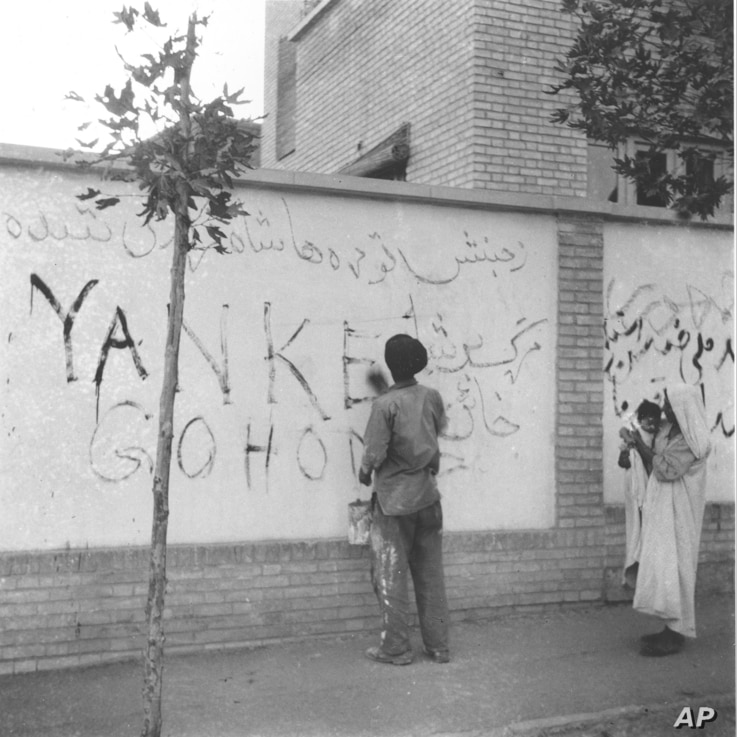 """A resident of Tehran washes """"Yankee Go Home"""" graffiti from a wall in the capital city of Iran, Aug. 21, 1953.  The new Premier Gen. Fazlollah Zahedi requested the cleanup after the coup d'etat, which restored the Shah of Iran in power."""