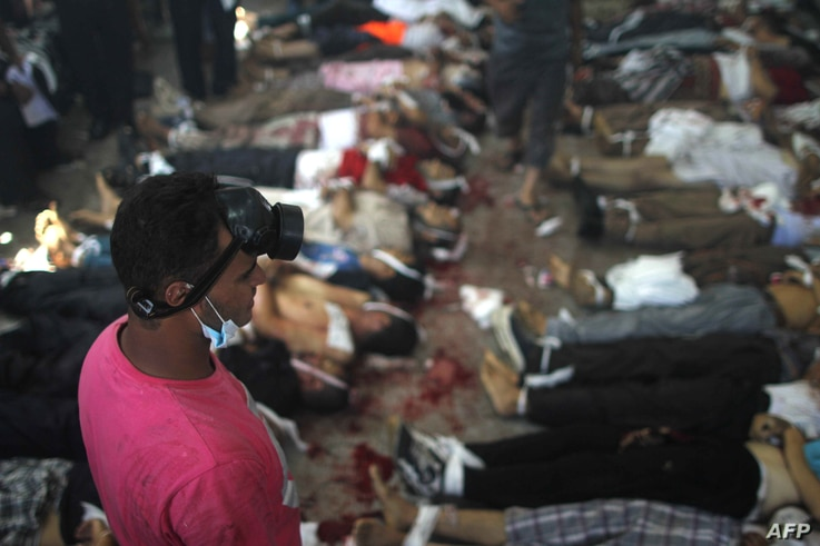 A man looks at bodies laid out in a make shift morgue after Egyptian security forces stormed two huge protest camps at the Rabaa al-Adawiya and Al-Nahda squares where supporters of ousted president Mohamed Morsi were camped,  in Cairo, on August 14,
