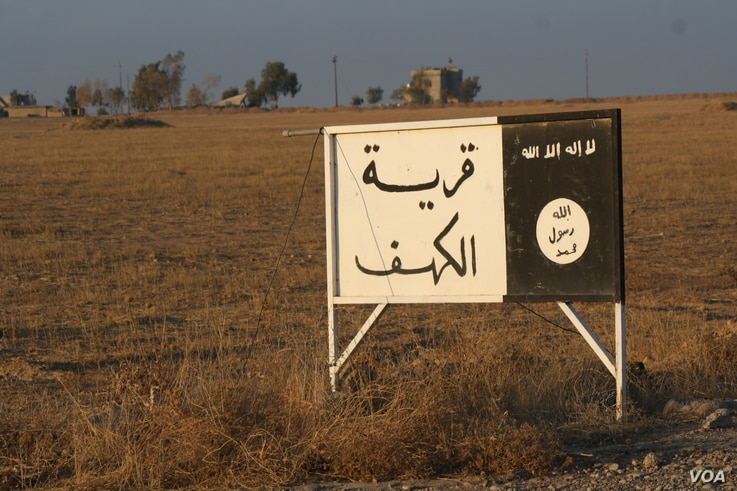 """While coalition airstrikes rain down on IS in Mosul, soldiers say the Iraqi Army's southern front is largely a ground operation pushing slowly towards the city.  This old IS road sign at least 50 kilometers from Mosul still stands, saying """"The Villag..."""