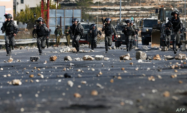Israeli security forces clash with Palestinian protestors in the West Bank city of Ramallah on December 11, 2017 as demonstrations continue to flare in the Middle East and elsewhere over US President Donald Trump's declaration of Jerusalem as Israel'...