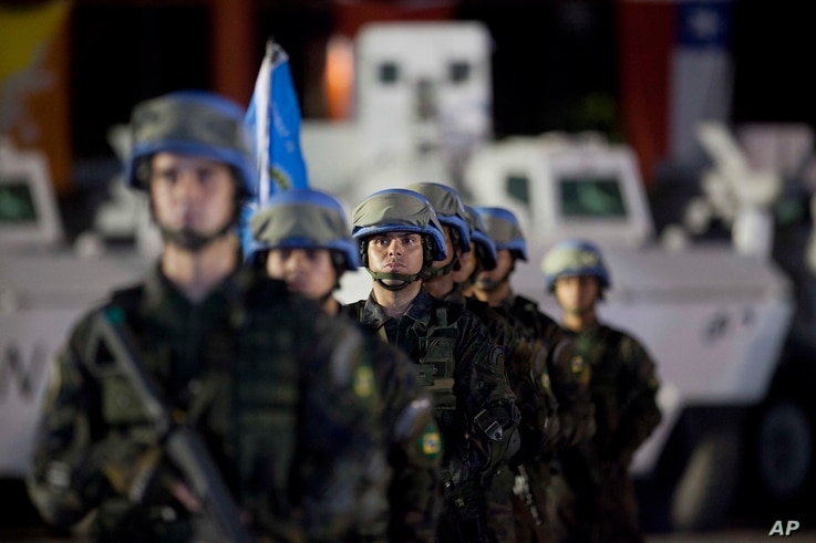 FILE - United Nations peacekeepers from Brazil stand at attention during the end of operations ceremony of the Brazilian battalion and engineering company, from the United Nations Stabilization Mission in Haiti, in Port-au-Prince, Aug. 31, 2017.