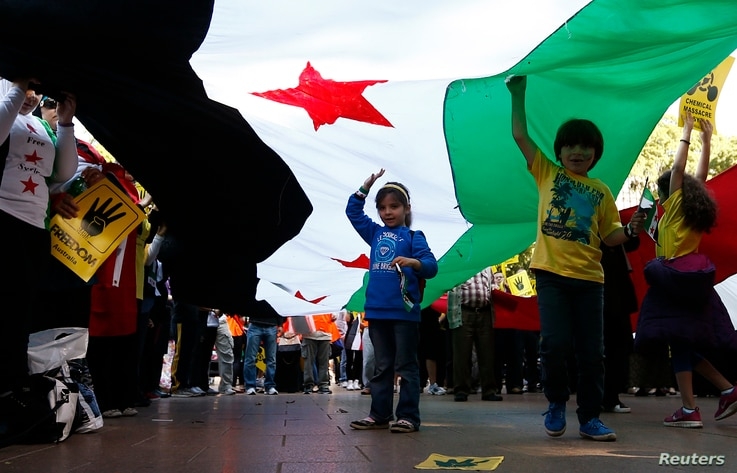 Children hold up a Syrian Opposition flag during a rally against the government of Syria and Egypt in central Sydney, Sept. 1, 2013.
