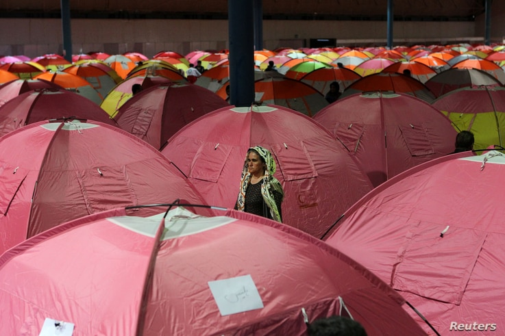 A woman surveys her surroundings as people take shelter at a stadium after a flooding in Golestan province, Iran, March 24, 2019.