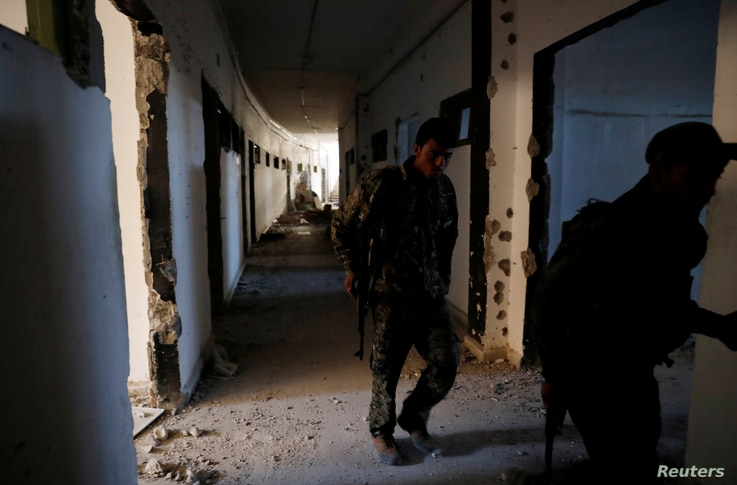 Fighters of Syrian Democratic Forces inspect the bunker of the Islamic State militants under the stadium in Raqqa, Syria Oct. 18, 2017.