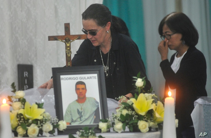 Angelita Muxfeldt, left, a cousin of Brazilian death row convict Rodrigo Gularte, touches Gularte's coffin at a funeral home in Jakarta, Indonesia, Wednesday, April 29, 2015. Indonesia brushed aside last-minute appeals and executed eight people convi...