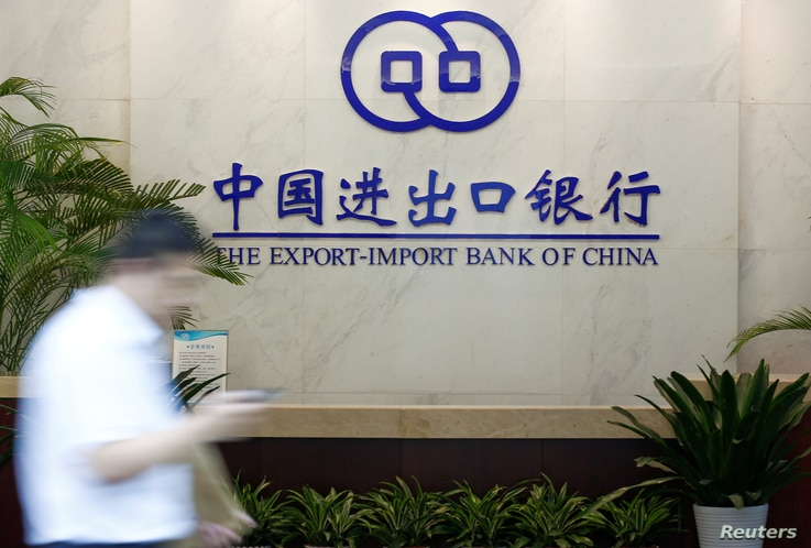 """FILE - A man walks past the lobby of the Export-Import Bank of China (EXIM) headquarters in Beijing, June 13, 2017. """"ExIm has become more risk-averse for new projects,"""" said Yunnan Chen, a researcher at the China Africa Research Initiative at SA..."""