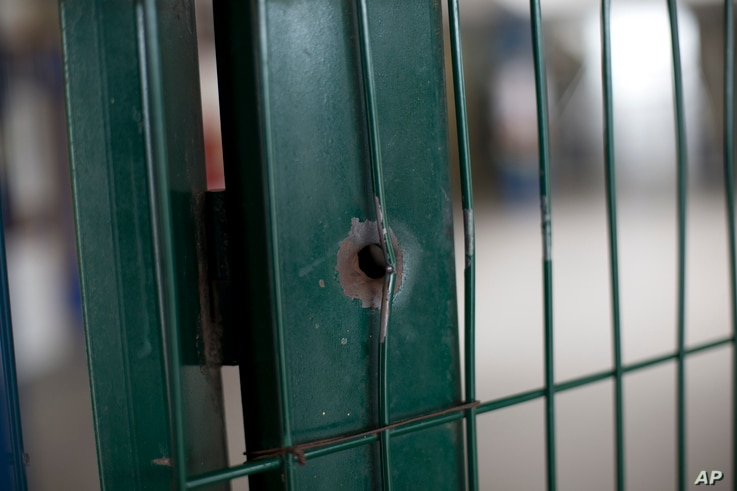 This April 12, 2017, photo shows a bullet hole on the front gate of a school in Acari, Rio de Janeiro, Brazil, where 13-year-old Maria Eduarda Conceicao was shot and killed when she was caught in the crossfire of a lengthy shootout between police and...