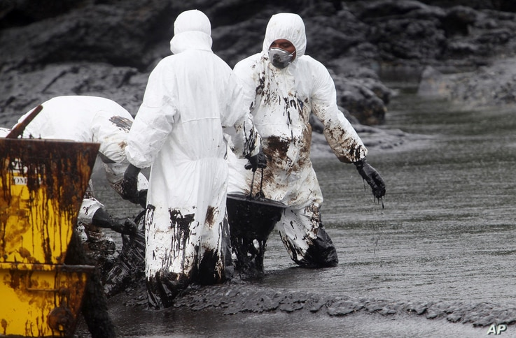 Workers remove crude oil during a clean up operation on the beach of Prao Bay on Samet Island in Rayong province eastern Thailand, July 30, 2013. About 50,000 liters (13,200 gallons) of crude oil that leaked from a pipeline operated by PTT Global Che...