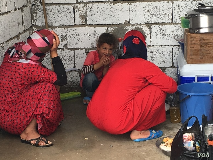 Women who fled IS hide their faces as they work in a makeshift kitchen in a refugee camp outside Makhmour, Iraq, April 11, 2016. (S. Behn/VOA)