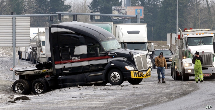 Truck driver Brad Cottle, left, from Florida, surveys the situation with his truck stuck in a ditch with tow truck driver Donny Callahan in Troutdale, Ore., Jan. 18, 2017. An ice storm shut down parts of major highways and interstates Wednesday in Or...