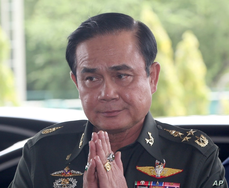 Thai Army Chief Gen. Prayuth Chan-Ocha greets back his junior upon his arrival at army club for a meeting with high ranking officials after declaring martial law Tuesday, May 20, 2014 in Bangkok, Thailand. Thailand's army declared martial law before ...