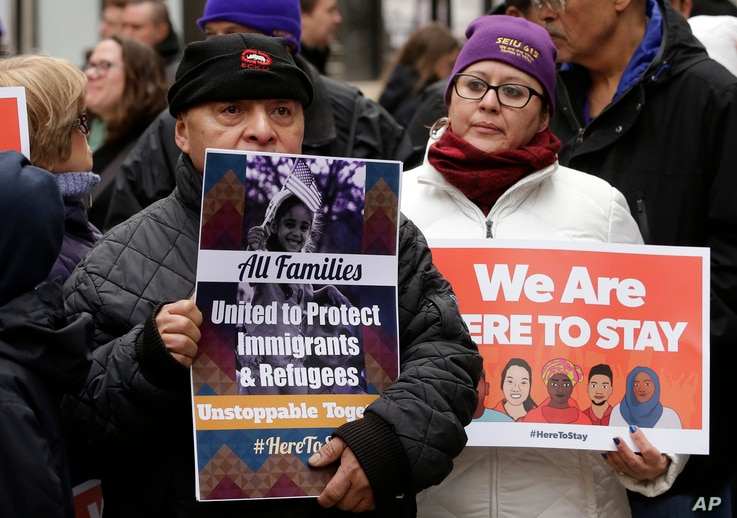 """Wilfredo Mendoza of Boston, left, and Christina Villafranca of Malden, Mass., display placards during a rally called """"We Will Persist"""" in Boston, Feb. 21, 2017. According to organizers, the rally was held to send a message to Republicans in Congress ..."""