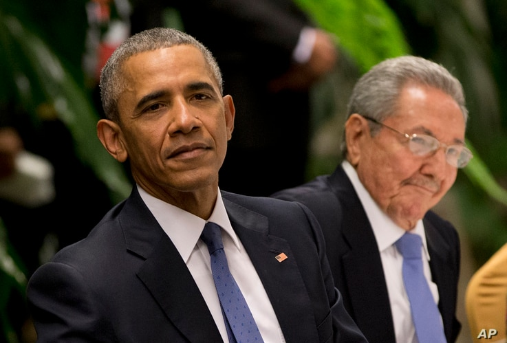 President Barack Obama, left, listens to a live band along with Cuba's President Raul Castro during a state dinner at the Palace of the Revolution in Havana, Cuba, March 21, 2016.