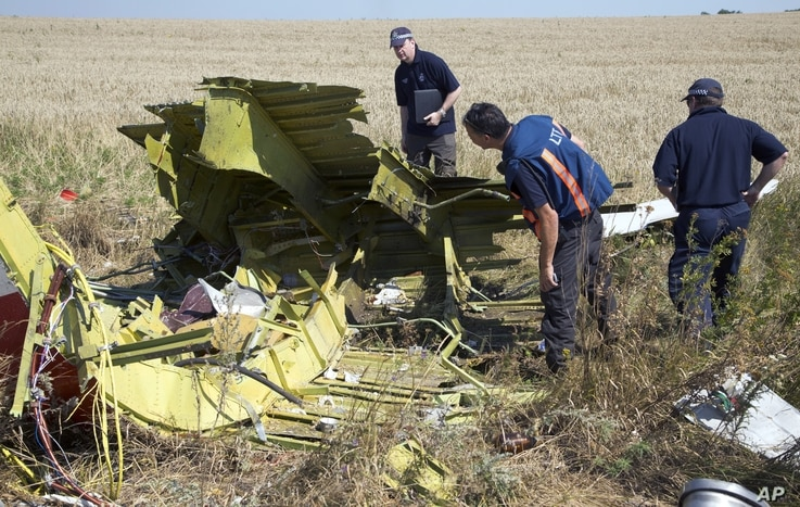 Australian and Dutch experts examine pieces of the Malaysia Airlines Flight 17 plane,  in the village of Hrabove, Donetsk region, eastern Ukraine Friday, Aug. 1, 2014. The investigators from the Netherlands and Australia plus officials with the Organ...