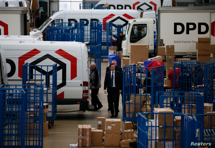 FILE - Britain's Chancellor of the Exchequer George Osborne walks past delivery vans during a visit to the DPD parcels depot in Raunds, Britain, May 6, 2015.