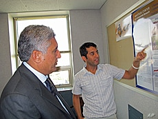 Purdue graduate student Mirwais Rahimi, from Herat Province, presents his research findings to Afghanistan's Minister of Agriculture Asif Rahimi (no relation).