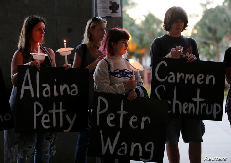 Participants hold placards with the names of victims of the shooting in Parkland, Florida, during a candlelight vigil at Florida Atlantic University in Boca Raton, Florida, Feb. 16, 2018.