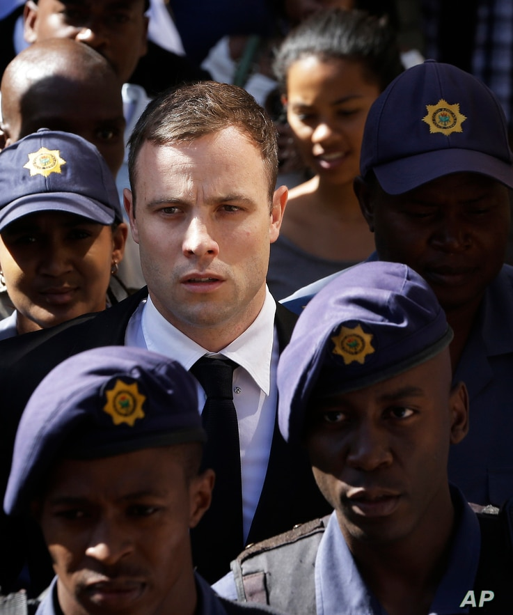 Oscar Pistorius, center, is escorted by police officers as he leaves the high court in Pretoria, South Africa, Thursday, Oct. 16, 2014. Following the testimony hearing, which is expected to end this week, Judge Thokozile Masipa will rule on what puni...