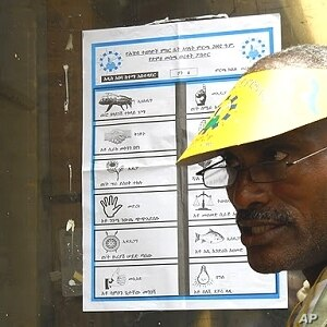 Before voters cast their ballots, election officials explain how to mark the ballot. Each symbol represents a different party, Addis Ababa, 23 May 2010
