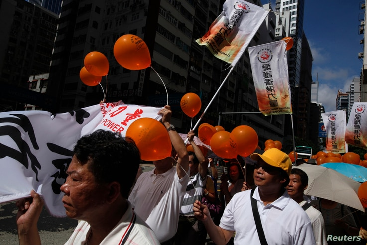 Supporters of Caring Hong Kong Power, a pro-China group, march  to the police headquarters during a demonstration against an unofficial referendum and the so-called Occupy Central protest movement in Hong Kong, June 29, 2014.