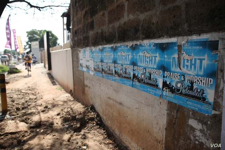 Posters promoting a nighttime religious revival are pictured alongside a busy road, in Accra, Ghana, Oct. 10,2014.(Chris Stein / VOA)