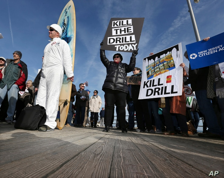 Scott Thompson, left, leans against his surfboard as he joins a gathering at a rally in Asbury Park, N.Y., to oppose federal plans that would allow oil and gas drilling in the Atlantic Ocean, Jan. 31, 2016. President Barack Obama has now designated t...