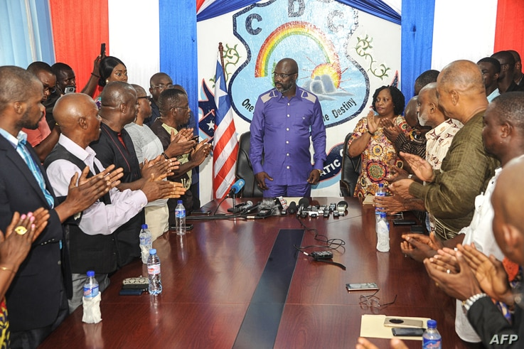 Former international soccer star Georges Weah is applauded as he arrives to speak to the press in the Liberian capital, Monrovia, on Dec, 30, 2017, the day after Liberia's elections board officially certified Weah as the winner of the nation's presid...