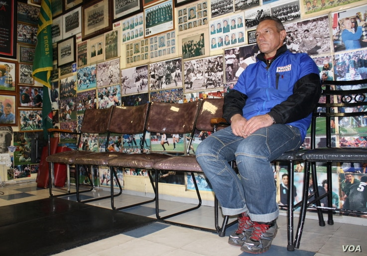 Barber Louis de Hart waits for a customer under a wall of rare rugby photographs. (Darren Taylor for VOA News)