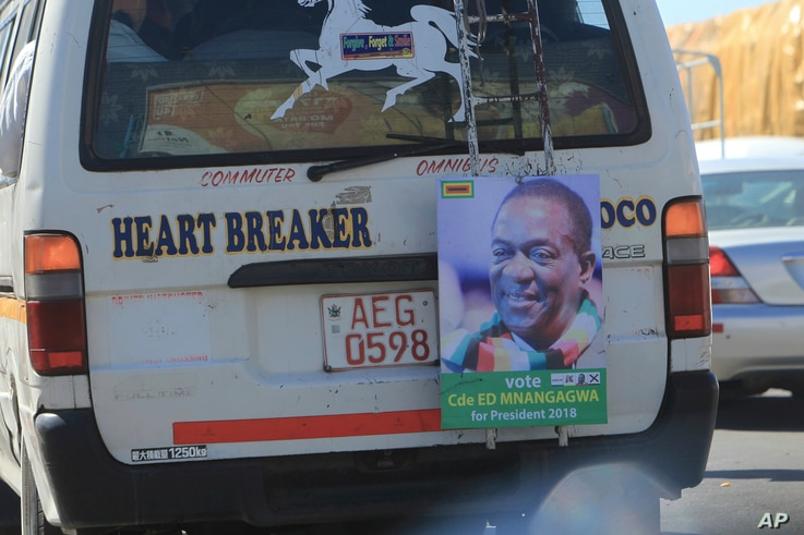 A portrait of Zimbabwe's President Emmerson Mnangagwa hangs from the back of a public transport vehicle on the streets of Harare, July, 27, 2018.