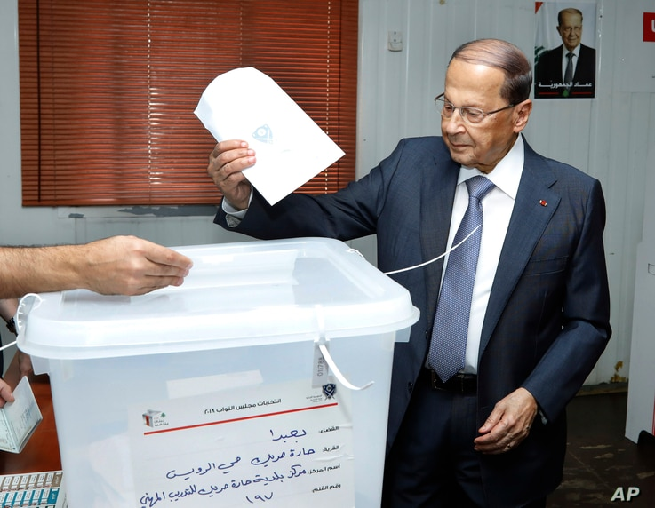 In this photo released by Lebanon's official government photographer Dalati Nohra, President Michel Aoun, casts his vote for Lebanon's parliamentary elections, at a ballot station, in the southern suburb of Beirut, May 6, 2018.