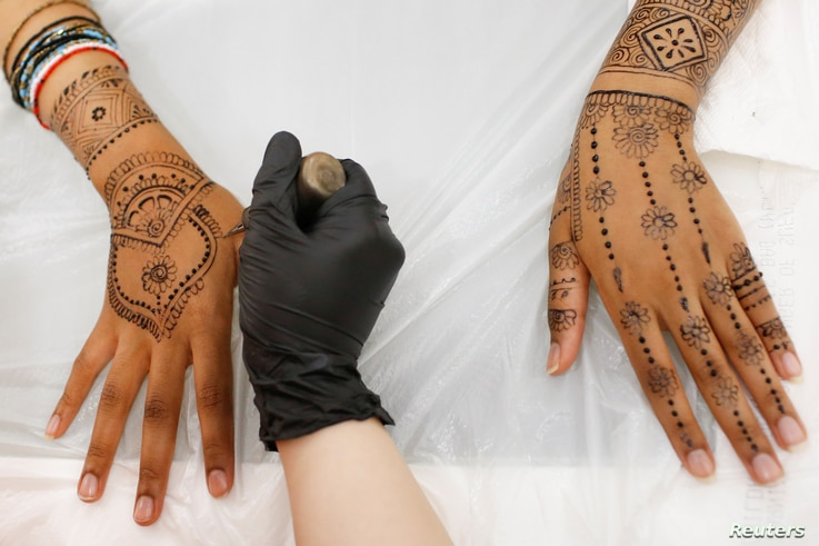 Henna is applied to the hands and arms of a customer at the Le'Jemalik Salon and Boutique ahead of the Eid al-Fitr Islamic holiday in Brooklyn, New York, June 21, 2017.