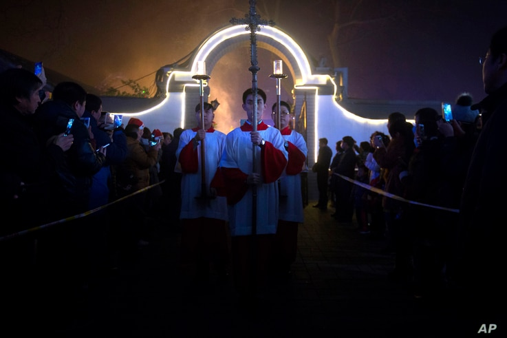 Cross-bearers process through the church grounds during a Christmas Eve mass at the Southern Cathedral, an officially-sanctioned Catholic church in Beijing, China, Thursday, Dec. 24, 2015.