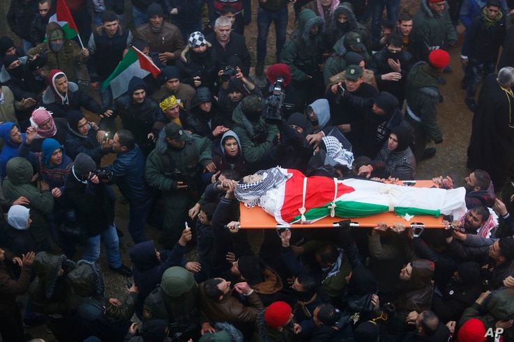 Palestinians carry the body of Saad al-Atrash to a hospital in the West Bank city of Hebron, Jan.1, 2016. The Israeli military transferred 23 bodies of Palestinians it says were involved in violence to their families in the West Bank.