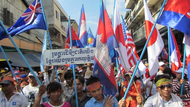 Young opposition supporters hold flags of major donor countries to Cambodia urging them to support their calls for an independent investigation into election irregularities, Phnom Penh, Oct. 23, 2013. (Khoun Theara/VOA Khmer)