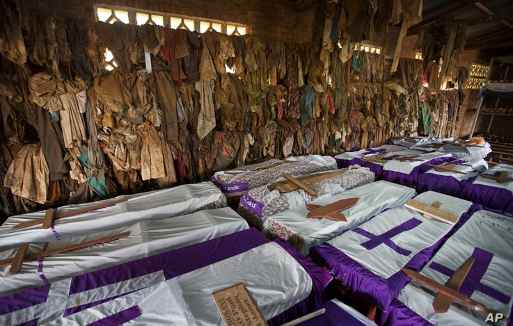 FILE - The clothes of some of those killed in Rwanda's genocide hang above coffins containing the remains of multiple victims at a memorial shrine at a Catholic church in Ntarama, Rwanda, April 4, 2014.
