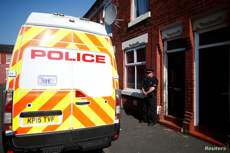 A police officer stand outside a property in Moss Side, following overnight raids in Manchester, Britain, May 25, 2017.