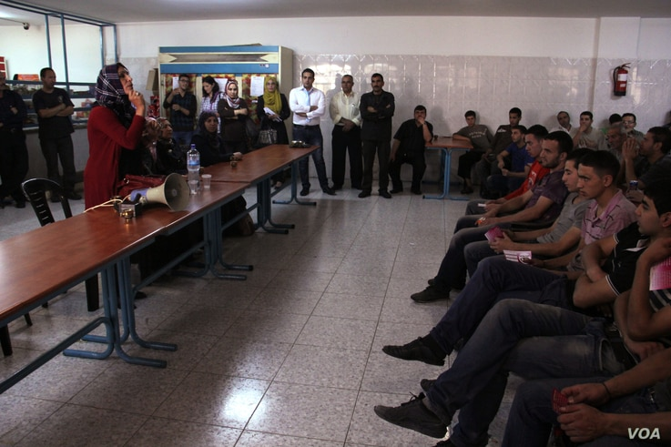 Maysoun Qawasmi talks to a crowd of workers at the Hibrawi mattress factory during a campaign for the upcoming Palestinian municipal elections. (VOA / R. Collard)