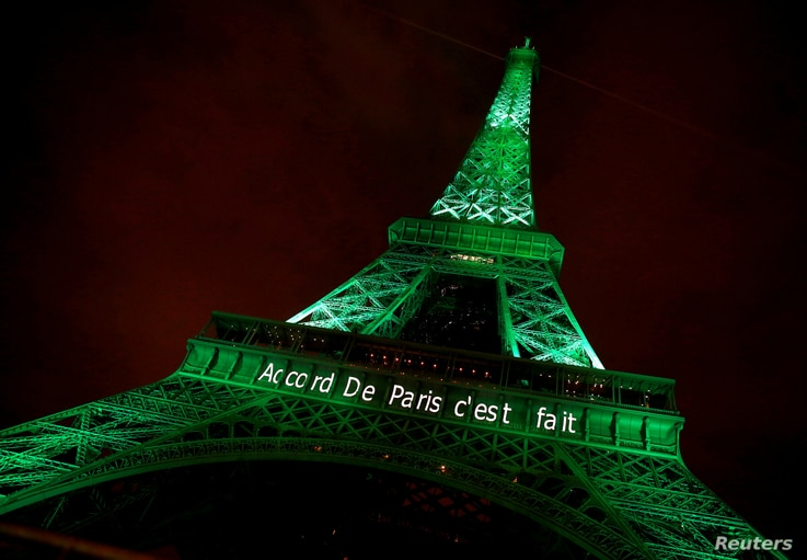 """FILE - The Eiffel tower is illuminated in green with the words """"Paris Agreement is Done,"""" to celebrate the Paris U.N. Climate Change agreement in Paris, France, Nov. 4, 2016."""