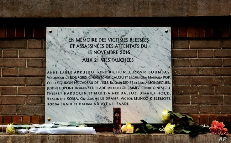 A commemorative plaque is seen next to La Belle Equipe restaurant, in Paris, Nov. 13, 2016. A year ago the Islamic State group brought its extremist war to Paris, seeding terror with attacks on a rock concert, the national stadium and bustling sidewa...