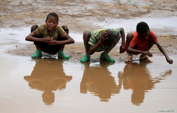 Children wash their heads with rain water in the village of Kobo, one of the drought stricken areas of Oromia region in Ethiopia, April 28, 2016.